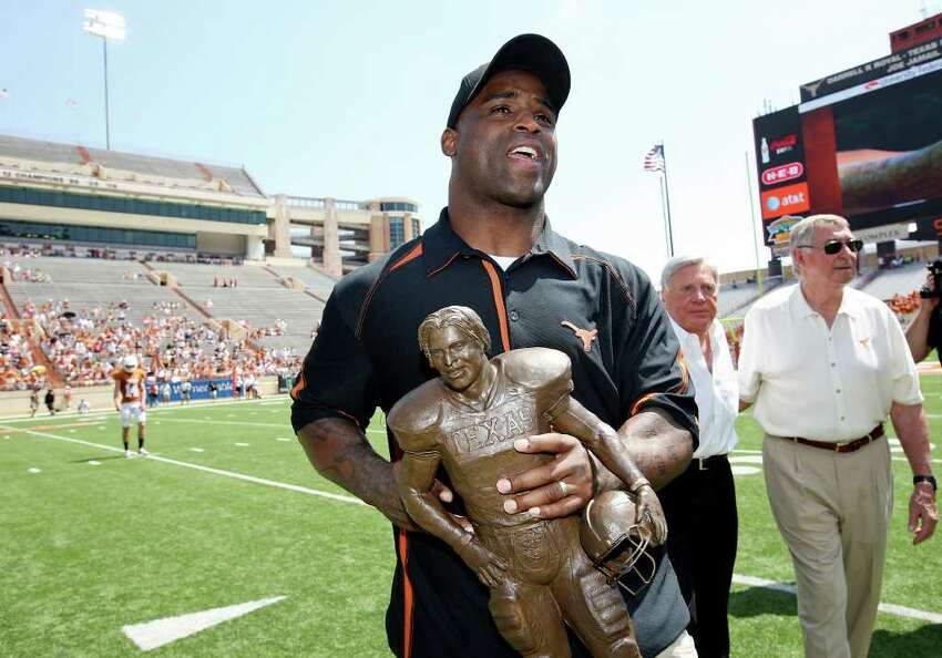 Former Longhorn and 1998 Heisman Trophy winner Ricky Williams carries a replica of his statue that was unveiled before the Orange-White Scrimmage Sunday, April 1, 2012 at Darrell K. Royal Texas Memorial Stadium in Austin.