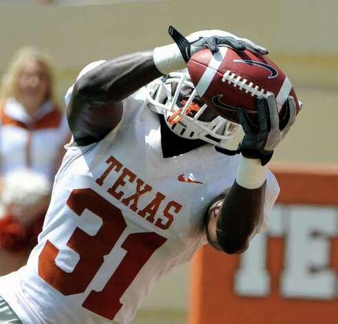 Texas cornerback Leroy Scott intercepts a pass during the second quarter of the team's Orange and White spring football game at Darrell K. Royal-Texas Memorial Stadium, Sunday, April 1, 2012, in Austin. Photo: Associated Press