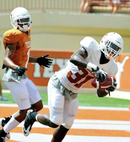 Texas cornerback Leroy Scott (31) intercepts a ball intended for wide receiver Mike Davis (1) during the second quarter of the Orange and White spring football game, Sunday, April 1, 2012, in Austin. Photo: Michael Thomas, Associated Press