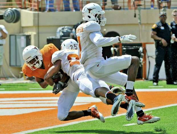 Texas wide receiver DeSean Hales (left) catches a touchdown pass against defensive backs Mykkele Thompson (right)  and Josh Turner (center) during the second quarter of the Orange and White spring football game, Sunday, April 1, 2012, in Austin. Photo: Michael Thomas, Associated Press