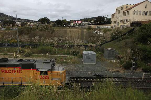 A train is seen heading into the train tunnel in front of the vacant Schlage Lock Company building (upper right) on Tuesday, March 27, 2012 in San Francisco, Calif.