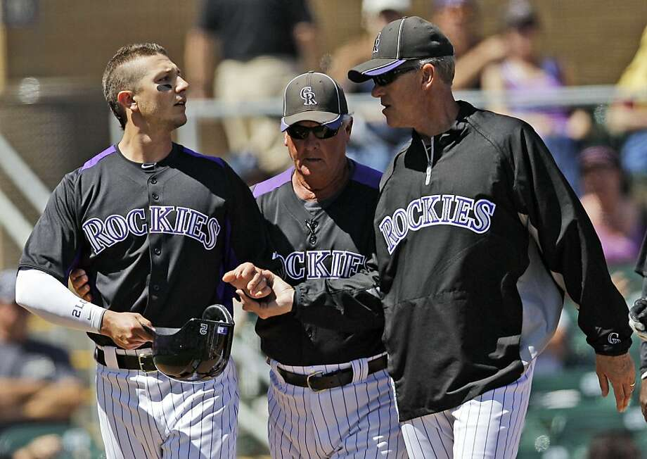 Colorado Rockies' Troy Tulowitzki, left, is held back by manager Jim Tracy, right, and coach Rick Matthews, center, after being hit by a pitch from Cleveland Indians starting pitcher Ubaldo Jimenez during the first inning of a spring training baseball game Sunday, April 1, 2012, in Scottsdale, Ariz. (AP Photo/Marcio Jose Sanchez) Photo: Marcio Jose Sanchez, Associated Press