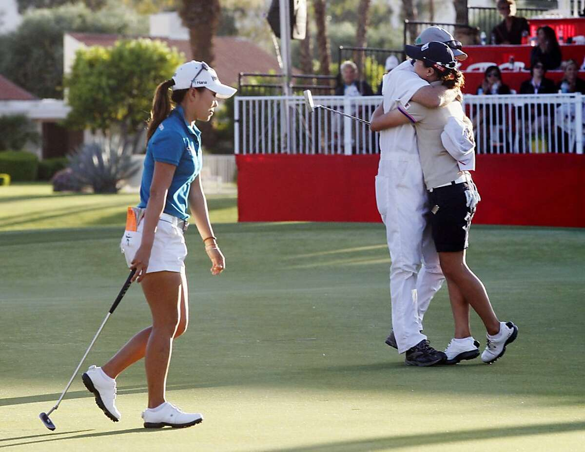 I.K. Kim, left, of South Korea, walks off the 18th green as Sun Young Yoo, of South Korea, and her caddie, Adam Woodward, celebrate after making the winning birdie putt in a sudden-death playoff during the final round of the Kraft Nabisco Championship golf tournament, Sunday, April 1, 2012, in Rancho Mirage, Calif. (AP Photo/Matt York)