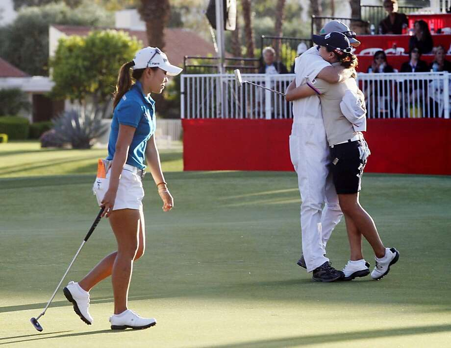 I.K. Kim, left, of South Korea, walks off the 18th green as Sun Young Yoo, of South Korea, and her caddie, Adam Woodward, celebrate after making the winning birdie putt in a sudden-death playoff during the final round of the Kraft Nabisco Championship golf tournament, Sunday, April 1, 2012, in Rancho Mirage, Calif. (AP Photo/Matt York) Photo: Matt York, Associated Press