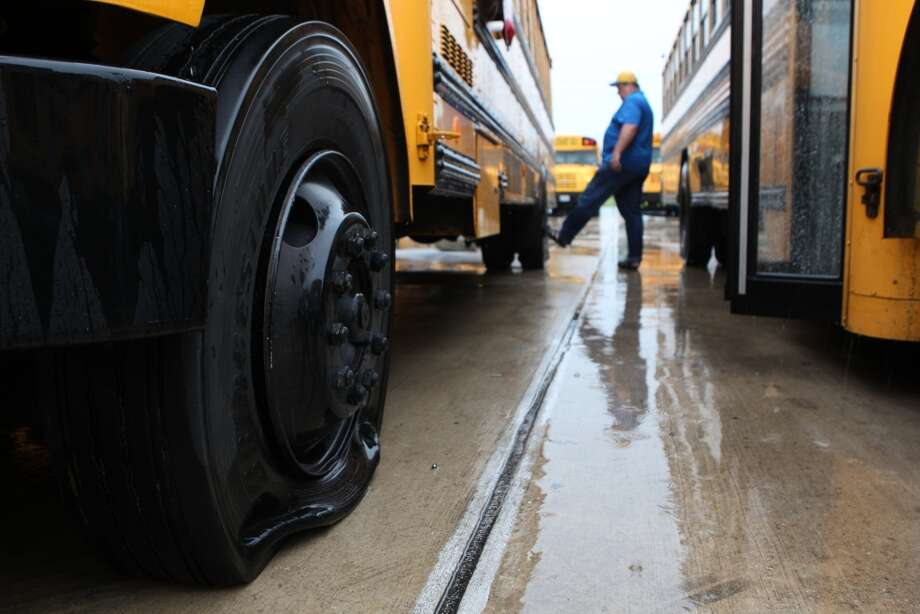 Bus driver Dave Cook kicks the tire on one of the 58 Crosby ISD school buses that had the valve stems cut leaving the tires flat. Photo: Johnny Hanson, Houston Chronicle