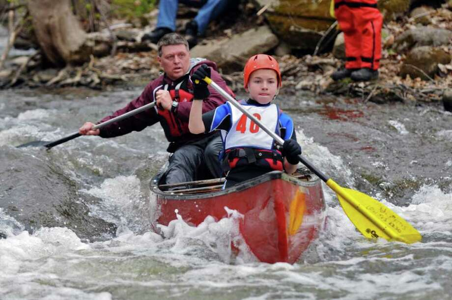 Danny Morris of Stillwater, 12, and his father Bob navigate the rapids during the 39th annual Tenandeho White Water Derby on Sunday April 1, 2012 in Mechanicville, NY.(Philip Kamrass / Times Union ) Photo: Philip Kamrass, Albany Times Union / 00016802A