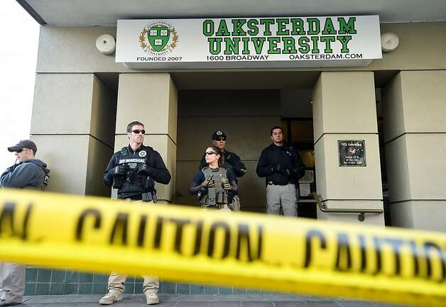 U.S. marshals stand at the entrance of Oaksterdam University in Oakland, Calif., on Monday, April 2, 2012. The federal agents raided the medical marijuana training school at the heart of California's pot legalization movement. (AP Photo/Noah Berger) Photo: Noah Berger, Associated Press