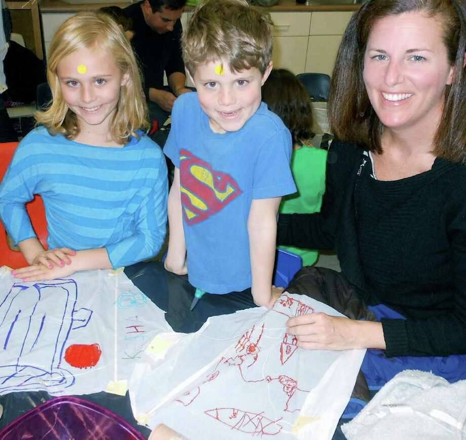 Grace, Zach and Betsy Taylor, of Westport, collaborate on making kites Saturday at Earthplace. Photo: Mike Lauterborn / Westport News contributed