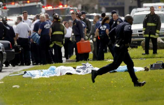 Emergency response officials looked over at the dead while a policeman ran by on Edgewater. Seven people were shot and killed at Oikos University in Oakland, Calif. Monday April 2, 2012. Photo: Brant Ward, The Chronicle