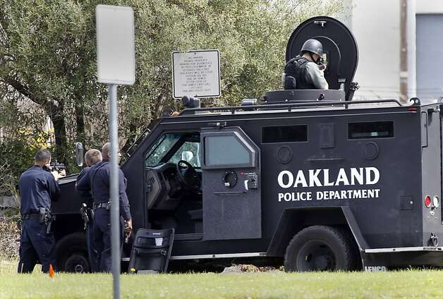 Police took cover behind a large tank as the suspect was being searched for. Seven people were shot and killed at Oikos University on Edgewater Street in Oakland, Calif. Monday April 2, 2012. Photo: Brant Ward, The Chronicle