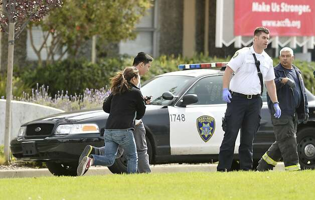An unidentified man and woman run past an Oakland Police car outside of Oikos University in Oakland, Calif., Monday, April 2, 2012. A suspect was detained Monday in a shooting attack at a California Christian university that sources said has left seven people dead. (AP Photo/Noah Berger) Photo: Noah Berger, Associated Press