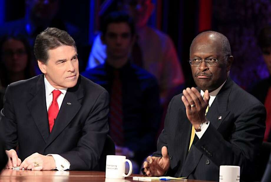 Herman Cain speaks while Rick Perry during a presidential debate sponsored by Bloomberg and The Washington Post held at Dartmouth College in Hanover, N.H., on Tuesday, Oct. 11, 2011.  (Andrew Harrer / Bloomberg)