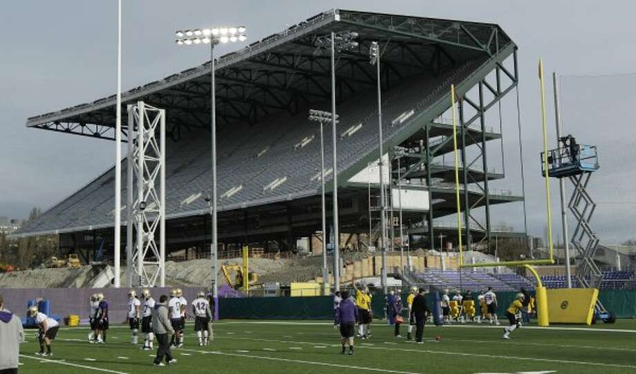 As the renovation of Husky Stadium continues behind them, Washington football players take part in the first day of spring football practice on Monday, April 2, 2012, in Seattle. The team will play their games this season at CenturyLink Field. (Ted S. Warren / Associated Press)