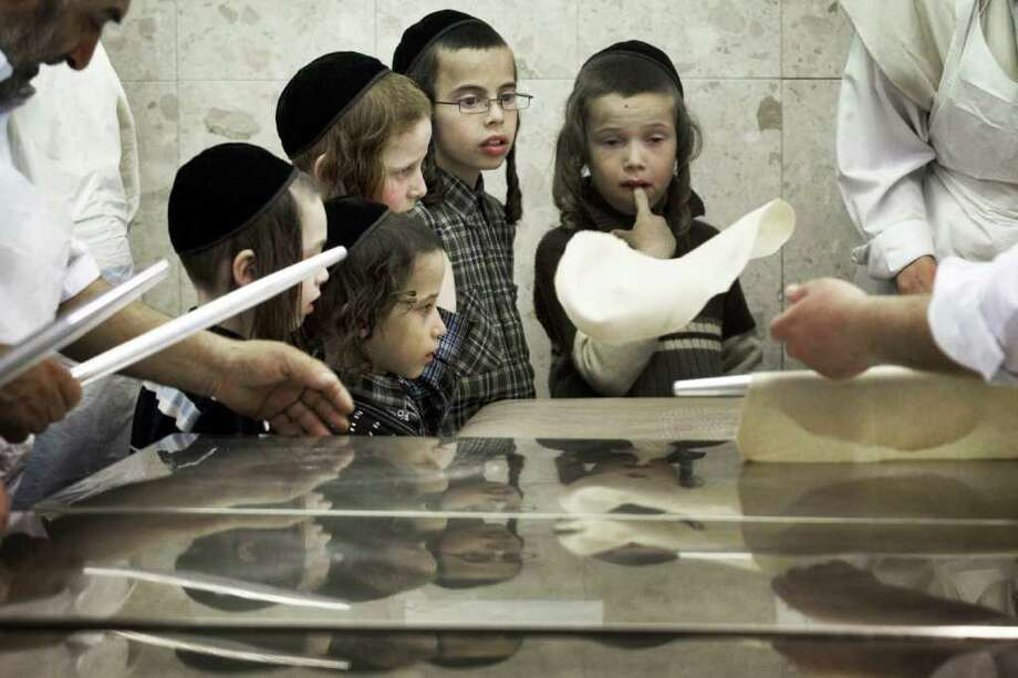 Children look on as Ultra-Orthodox Jewish men knead the dough before baking the Matzoth or unleavened bread on April 2, 2012 in Jerusalem. Religious Jews throughout the world eat matzoth during the eight-day Pesach holiday (Passover). Photo: MENAHEM KAHANA, AFP/Getty Images / 2012 AFP