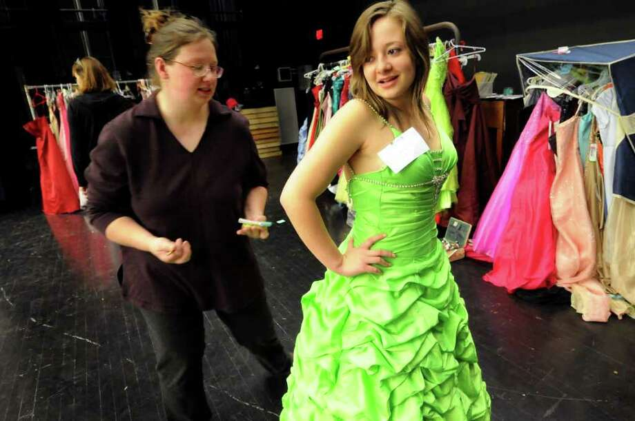 Sam Martin, 17, right, tries on a prom dress as Leslie Chotkowski of Schoharie looks to make alterations on Friday, March 30, 2012, at Schoharie High in Schoharie, N.Y. More than 300 dresses were collected around the Capital Region to help make prom possible for the flood-stricken town. Through residents' generosity, prom will be May 18 at the Appel Inn in Guilderland. There's still a need for tuxedos for the boys. To donate, visit www.projectcinderella.net or www.nydisasterrelief.org. (Cindy Schultz / Times Union) Photo: Cindy Schultz / 00017037A