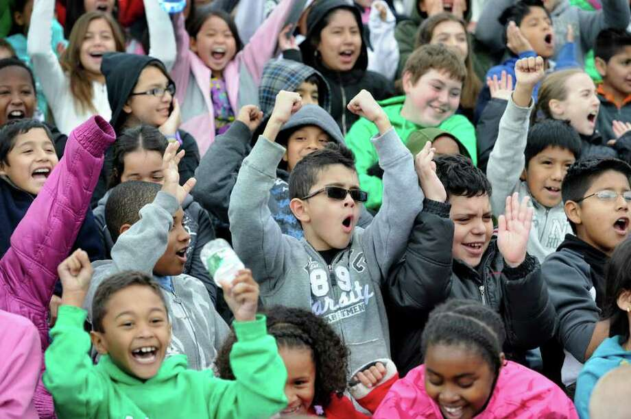 Diago Souza, 8, center, a Park Avenue School student, lets out a cheer with fellow elementary school kids prior to the start of a KidsMarathon kickoff on the track at Danbury High School Monday morning, April 2, 2012. Photo: Carol Kaliff / The News-Times