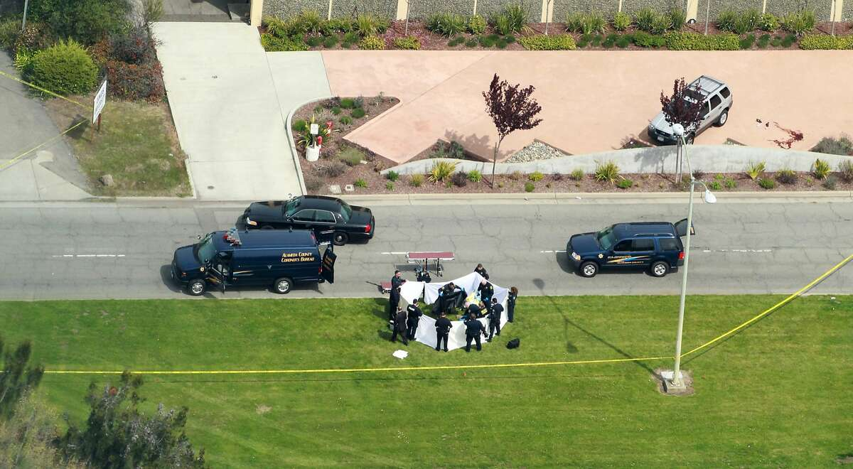 Officers from the Alameda County Sheriff Coroner Department remove the bodies from outside the Oikos University, Monday April 2, 2012, in Oakland, Calif.