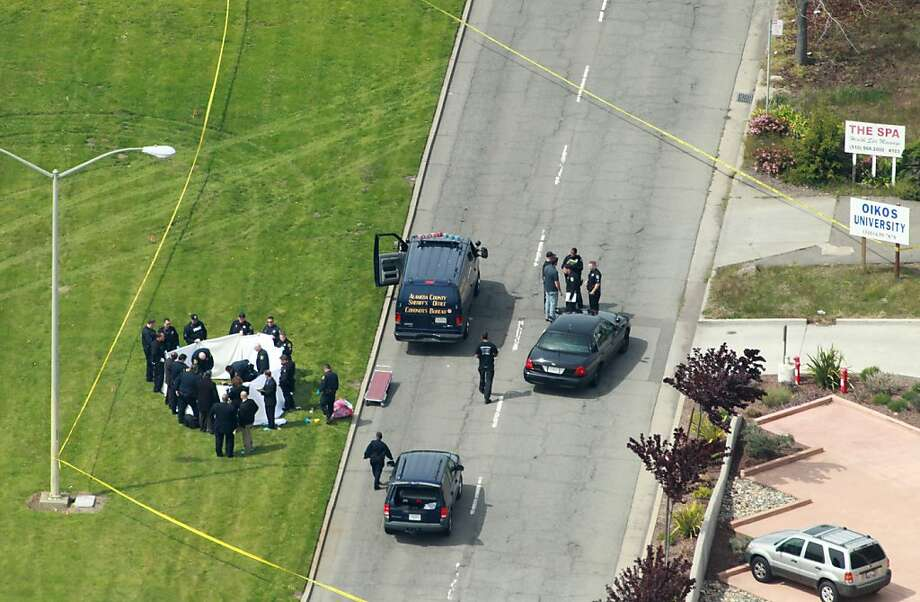 Officers from the Alameda County Sheriff Coroner  Department remove the bodies from outside the Oikos University, Monday April 2, 2012, in Oakland, Calif. Photo: Lacy Atkins, The Chronicle