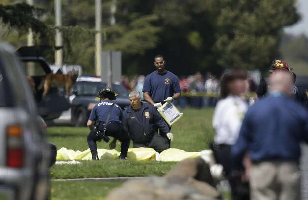Emergency responders kneel by bodies covered on Edgewater Road on Monday, April 2, 2012 in Oakland, Calif. Authorities have confirmed that seven people have been killed by a gunman at a Oikos University in Oakland. Photo: Lea Suzuki, The Chronicle