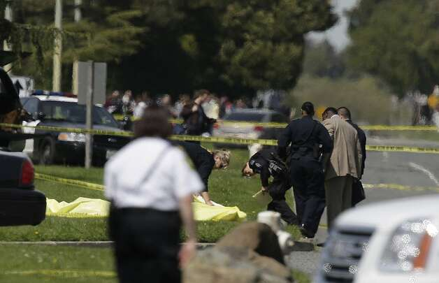 Police inspect bodies covered on Edgewater Road on Monday, April 2, 2012 in Oakland, Calif. Authorities have confirmed that seven people have been killed by a gunman at a Oikos University in Oakland. Photo: Lea Suzuki, The Chronicle