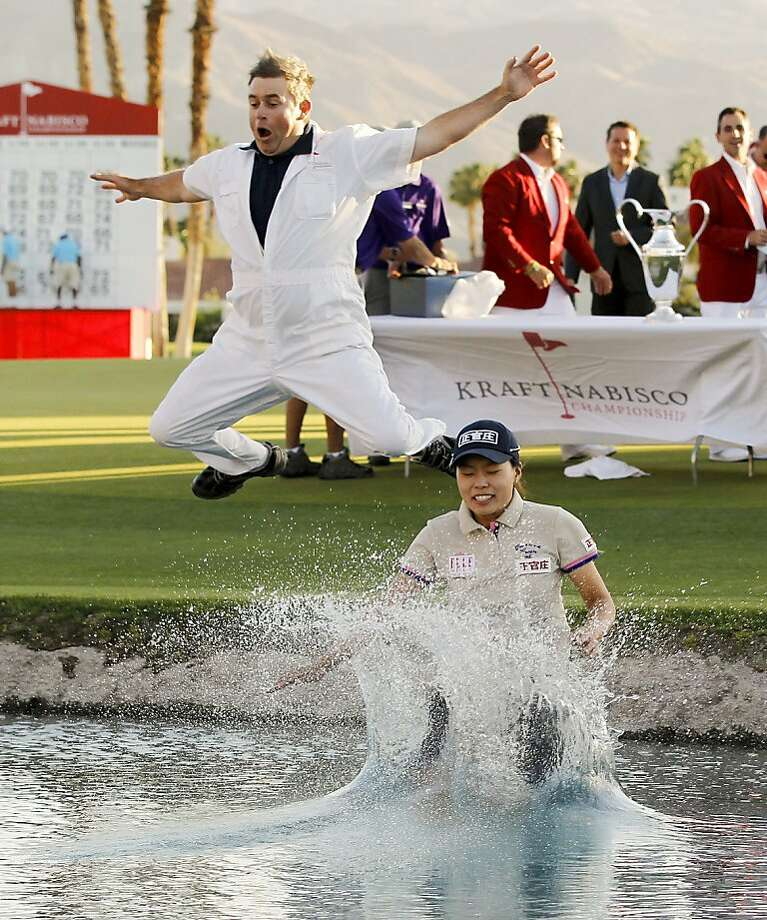 Double dipping: Sun Young Yoo and caddie Adam Woodward leap into a water hazard after Sun's playoff win during the final round of the LPGA Kraft Nabisco Championship in Rancho Mirage, Calif. Photo: Chris Carlson, Associated Press
