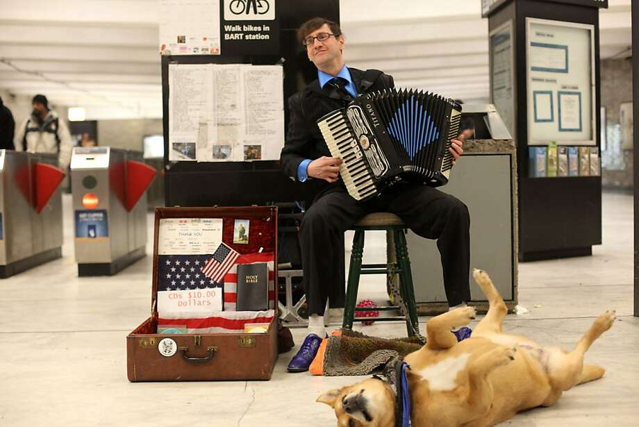 A regular fixture during the early morning commute hours, Robert V Doerr Jr., with his service dog named Ginger, plays his accordion at the Civic Center BART station on Monday April 2, 2012 in San Francisco, Calif. Photo: Mike Kepka