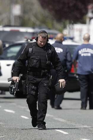 An officer carries a gun as he walks on Edgewater Road on Monday, April 2, 2012 in Oakland, Calif. Authorities have confirmed that seven people have been killed by a gunman at a Oikos University in Oakland. Photo: Lea Suzuki, The Chronicle