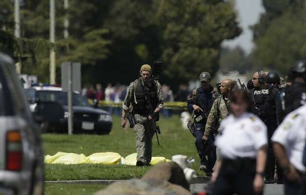 Police and officials walk on Edgewater Road near bodies of victims from the shooting at Oikos University on Monday, April 2, 2012 in Oakland, Calif. Authorities have confirmed that seven people have been killed by a gunman at a Oikos University in Oakland. Photo: Lea Suzuki, The Chronicle