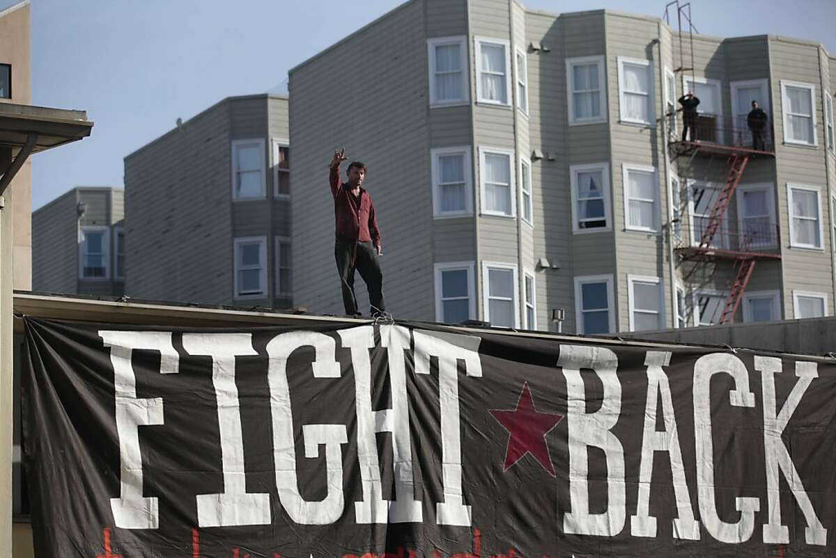 Occupy protester Nick Shaw waves to people below him as he stands atop 888 Turk Street the day after the building had been taken over by protesters on Monday, April 2, 2012 in San Francisco, Calif.