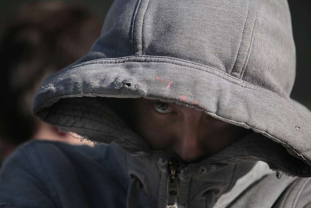 An Occupy protester peeks out from beneath a hood while standing in front of 888 Turk Street which had been taken over the day before on Monday, April 2, 2012 in San Francisco, Calif.
