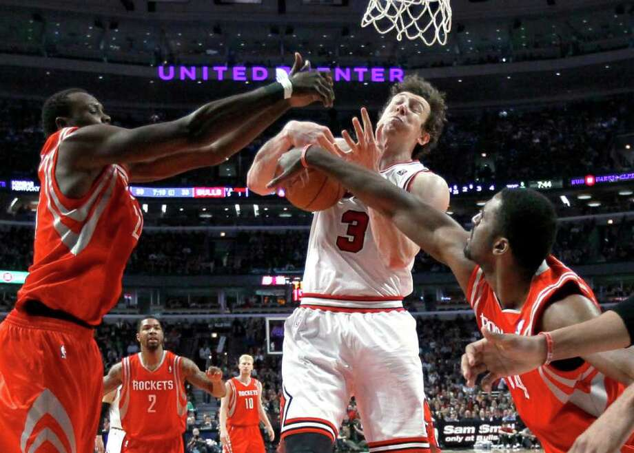 Chicago Bulls center Omer Asik (3) tries to pull in a rebound between Houston Rockets center Samuel Dalembert, left, and forward Patrick Patterson during the first half of an NBA basketball game Monday, April 2, 2012, in Chicago. (AP Photo/Charles Rex Arbogast) Photo: Charles Rex Arbogast, Associated Press / AP