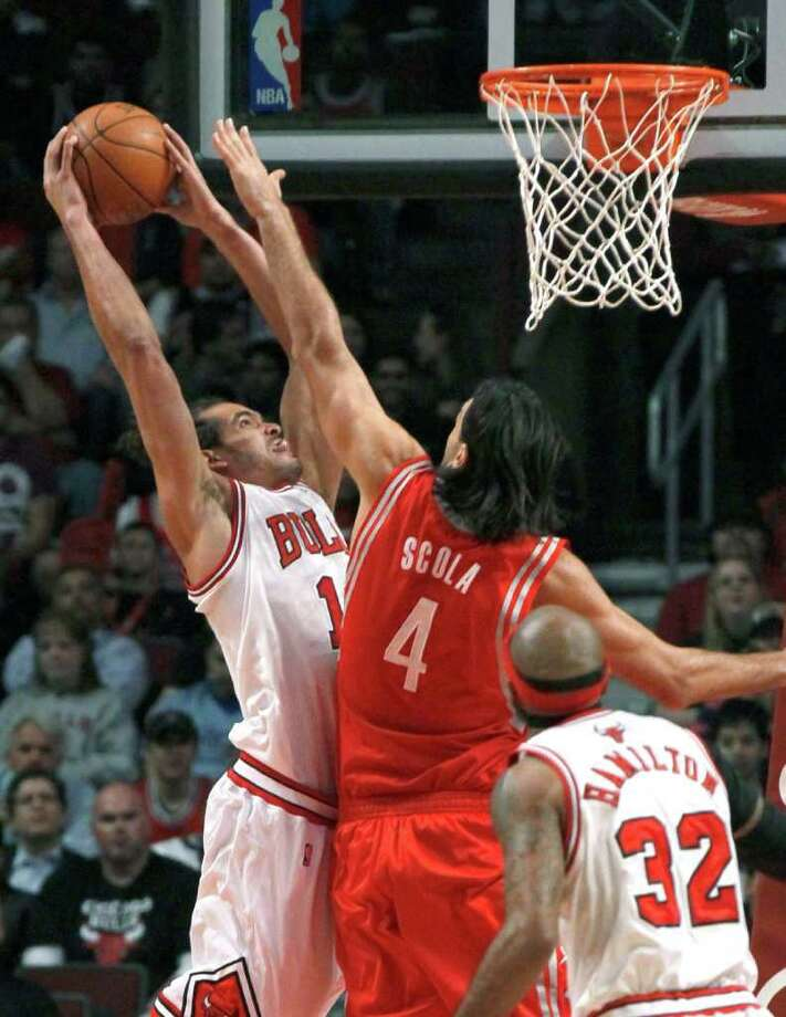 Chicago Bulls center Joakim Noah (13) dunks over Houston Rockets forward Luis Scola (4) as Richard Hamilton watches during the first half of an NBA basketball game Monday, April 2, 2012, in Chicago. (AP Photo/Charles Rex Arbogast) Photo: Charles Rex Arbogast, Associated Press / AP