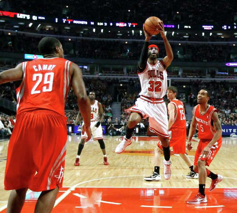Chicago Bulls guard Richard Hamilton (32) shoots between Houston Rockets center Marcus Camby (29) and guard Courtney Lee during the first half of an NBA basketball game Monday, April 2, 2012, in Chicago. (AP Photo/Charles Rex Arbogast) Photo: Charles Rex Arbogast, Associated Press / AP