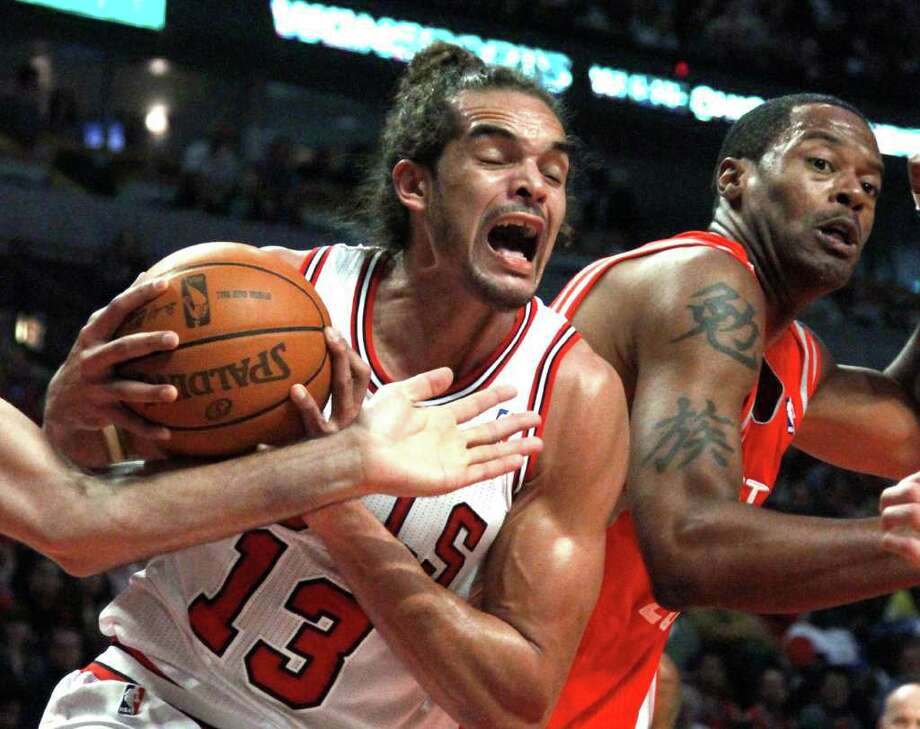 Chicago Bulls center Joakim Noah (13) grabs a rebound next to Houston Rockets center Marcus Camby during the first half of an NBA basketball game Monday, April 2, 2012, in Chicago. (AP Photo/Charles Rex Arbogast) Photo: Charles Rex Arbogast, Associated Press / AP
