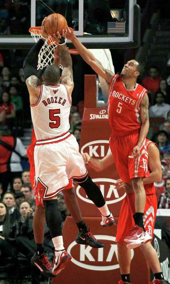Houston Rockets guard Courtney Lee, right, blocks the shot of Chicago Bulls forward Carlos Boozer during the first half of an NBA basketball game Monday, April 2, 2012, in Chicago. (AP Photo/Charles Rex Arbogast) Photo: Charles Rex Arbogast, Associated Press / AP