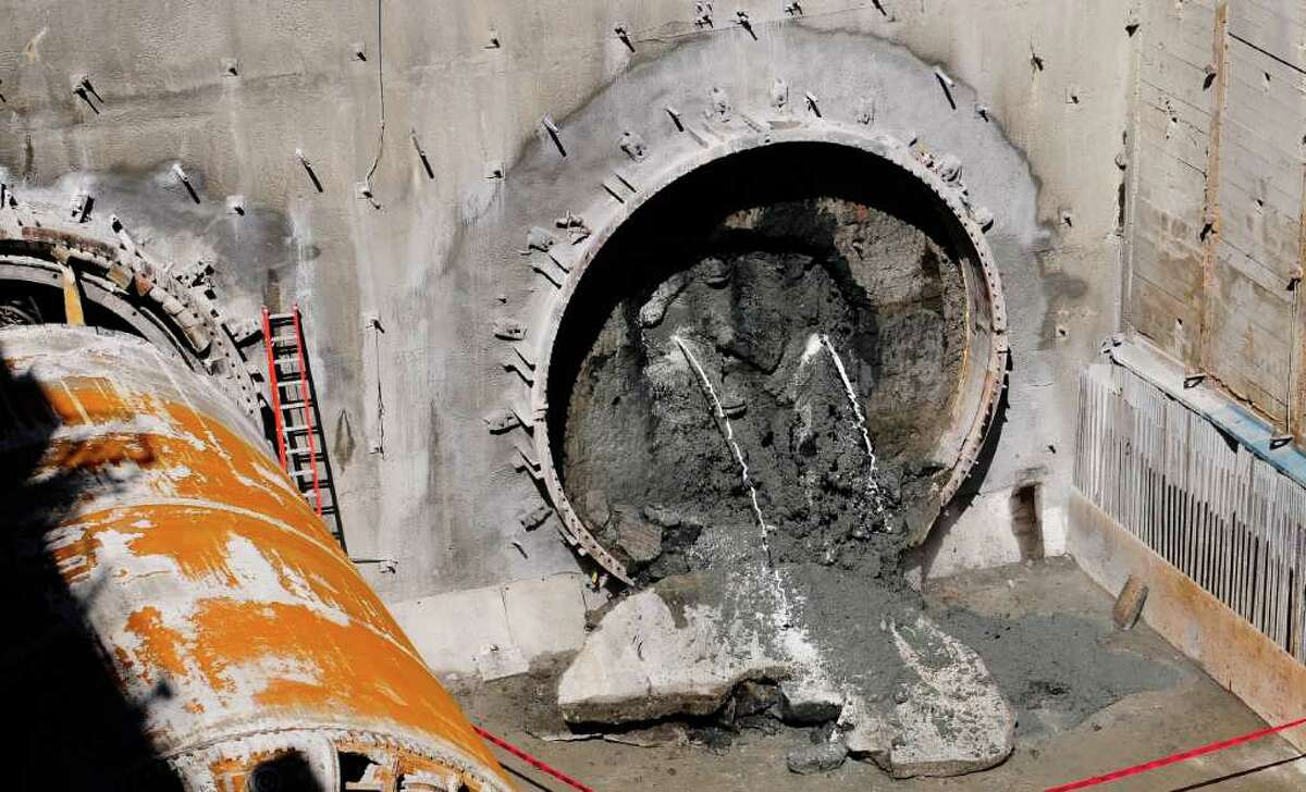 """Liquid jets out of the northbound tunnel as the tunnel boring machine """"Balto"""" knocks down the tunnel wall at the future University Link Capitol Hill site at E John St. on Monday, April 2, 2012. The machine finally broke through the second of two tunnels at 2:33 pm. The University Link, which goes under SR 520 and the Volunteer Park Water Tower, runs 2.15 miles from the University of Washington to Capitol Hill. The station is expected to open in 2016."""
