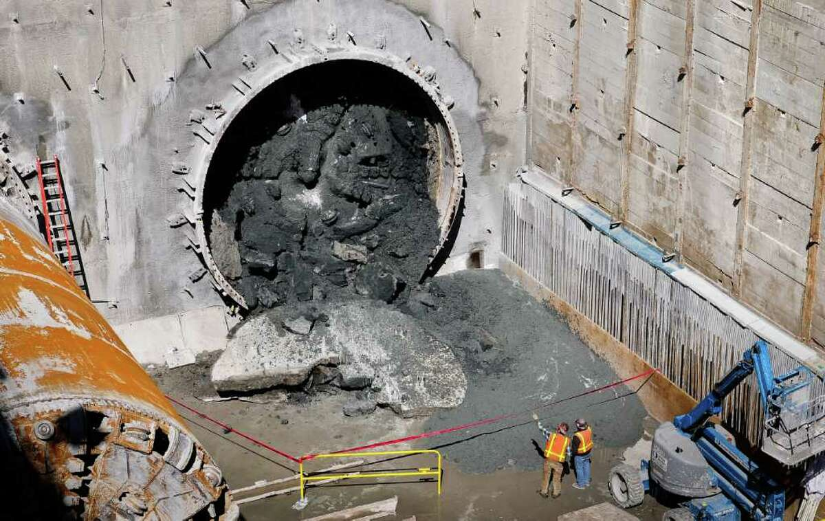 A worker points at the debris of the northbound tunnel wall at the future University Link Capitol Hill site at E John St. on Monday, April 2, 2012. The machine finally broke through the second of two tunnels at 2:33 pm. The University Link, which goes under SR 520 and the Volunteer Park Water Tower, runs 2.15 miles from the University of Washington to Capitol Hill. The station is expected to open in 2016.