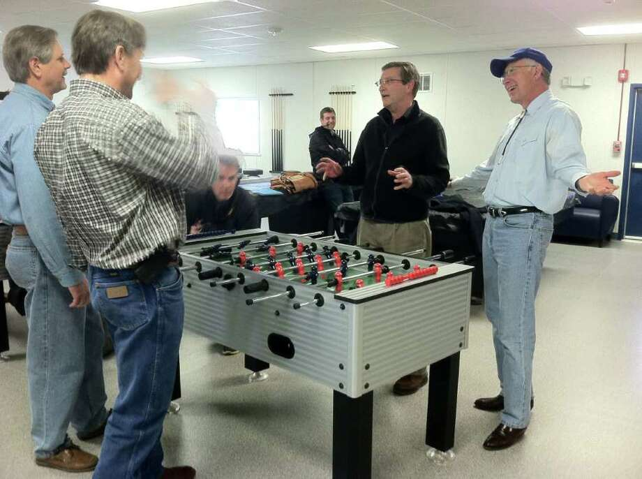From left, Sen. John Hoeven, R-N.D., Rep. Rick Berg, R-N.D., Sen. Kent Conrad, D-N.D. and Interior Secretary Ken Salazar joke during a game of foosball at a housing area for oil workers in Dickinson, N.D. Photo: Jennifer Dlouhy / Houston Chroni