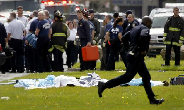 Emergency response officials looked over at the dead while a policeman ran by on Edgewater. Police are confirming that seven people were shot and killed at Oikos University on Edgewater Street in Oakland, Calif. Monday April 2, 2012. Photo: Brant Ward, The Chronicle