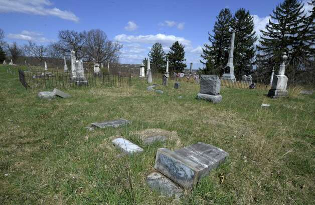 A gravestone is toppled across the lawn of the Hudson View Cemetery in Mechanicville and Halfmoon, N.Y., on April 2, 2012.  According to authorities,  vandalism at the cemetery could amount to $100,000 in damages.    (Skip Dickstein/Times Union archive) Photo: Skip Dickstein