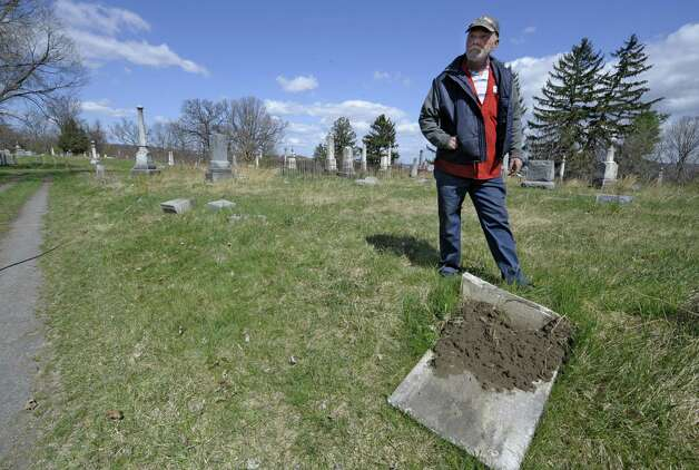 Caretaker Jim Doty stands by a toppled gravestone at the Hudson View Cemetery in Mechanicville and Halfmoon, N.Y., on April 2, 2012.  Vandalism at the cemetery could amount to $100,000 in damages.    (Skip Dickstein/Times Union archive) Photo: Skip Dickstein