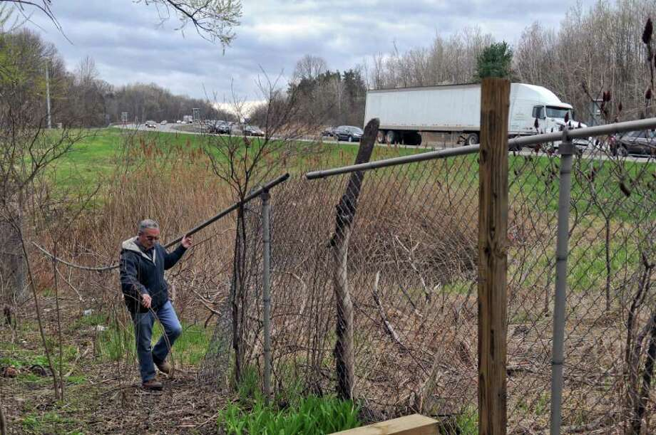 Dave Liney said that a driver recently crashed through his back fence and into his pickup truck parked nearby. He and his wife say they've seen an increase in crashes and other incidents on the road. He walks along the damaged fence in his yard, which borders the Northway, on Thursday March 29, 2012 in Latham, NY. (Philip Kamrass / Times Union ) Photo: Philip Kamrass / 00017017A