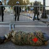 A protester lies on the ground outside of barricades at  Broadway and 14th Street on Monday morning, November 14, 2011 in Oakland, Calif.