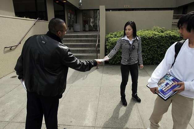 Cristhian Cortes (cq) an employee at American Indian Charter School II, hands a flyer to Miaochang Wu, center, and her son, Kenneth Ng, 15, as they leave The American Indian Charter School II, in Oakland, Calif., on Monday, April 2, 2012. The flyer explains that the school, one of the best middle school in California, could be shuttered at the end of the year because of financial impropriety. This charter school, has been touted nationally as a model of success. And now, it's facing scandal and investigations.. Photo: Carlos Avila Gonzalez, The Chronicle