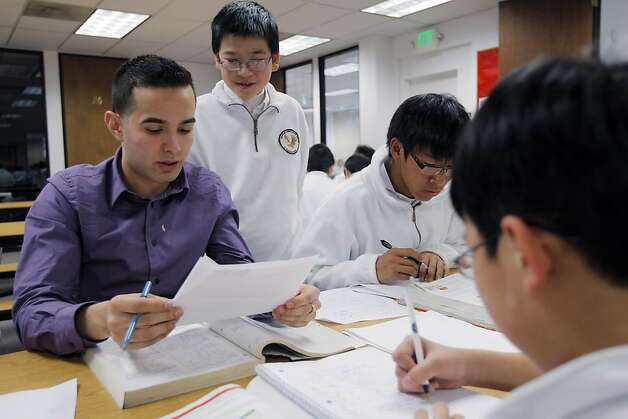 Jose Guzman, a tutor at The American Indian Charter School II, helps Justin Chen, 13, center, with his homework on Monday, April 2, 2012, in Oakland, Calif., as Henry Pan, 16, right, and Raymond Tan, 10, far right, study nearby. The school, one of the best middle school in California could be shuttered at the end of the year because of financial impropriety. This charter school, has been touted nationally as a model of success. And now, it's facing scandal and investigations.. Photo: Carlos Avila Gonzalez, The Chronicle