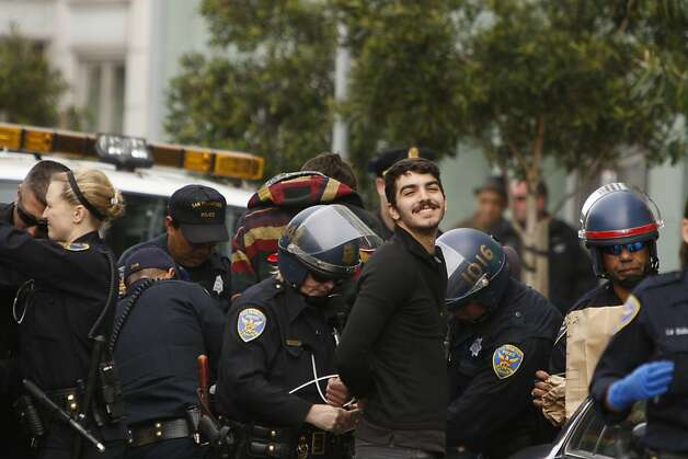 A demonstrator smiles as he is detained by officers outside the building. Photo: Siana Hristova, The Chronicle