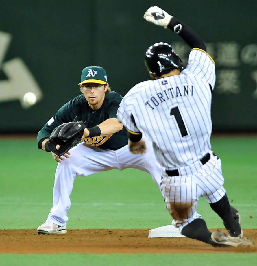 Oakland Athletics infielder Eric Sogard (L) waits for the throw to tag out Takashi Toritani (R) of Japan's Hanshin Tigers at second base during the 7th inning of their exhibition game in Tokyo on March 26, 2012.  Hanshin won 12-6.  The Seattle Mariners and Oakland Athletics are here ahead of an opening two-game series to start the 2012 Major League Baseball (MLB) season on March 28-29.        AFP PHOTO / KAZUHIRO NOGI (Photo credit should read KAZUHIRO NOGI/AFP/Getty Images) Photo: Kazuhiro Nogi, AFP/Getty Images