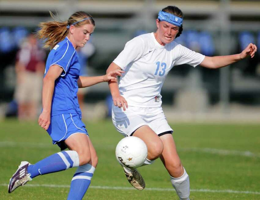 New Braunfels' Rebekah Kensing (left) and Johnson's Bridget Gleason (13) battle for a ball during a bidistrict playoff match between the Johnson Jaguars and the New Braunfels Unicorns at the Blossom Athletic Center West Soccer Field on Monday, April 2, 2012.