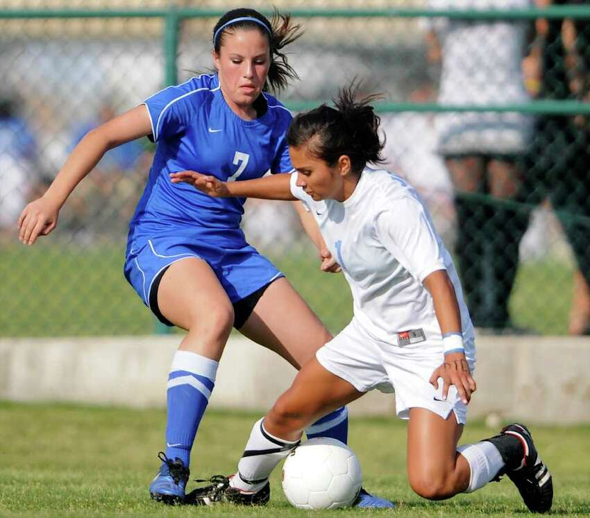 Johnson's Adriana Garcia (1) is tripped up by New Braunfels' Jennifer Trevino (7) during a bidistrict playoff match between the Johnson Jaguars and the New Braunfels Unicorns at the Blossom Athletic Center West Soccer Field on Monday, April 2, 2012.