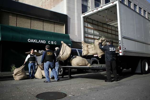 Federal agents carried bags of cannabis out of a building and into a truck, around the corner from the Oaksterdamn University and protestors. A federal raid took place at Oaksterdamn University in Oakland on Monday, April 2, 2012. Photo: Sean Culligan, The Chronicle